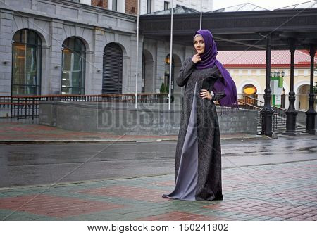 modern Muslim woman in beautiful Eastern dress standing on the background of the hotel. Ufa