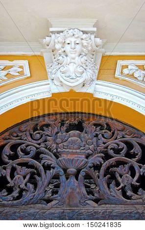 Statue of an angel above an artistic metal door in Quito Ecuador