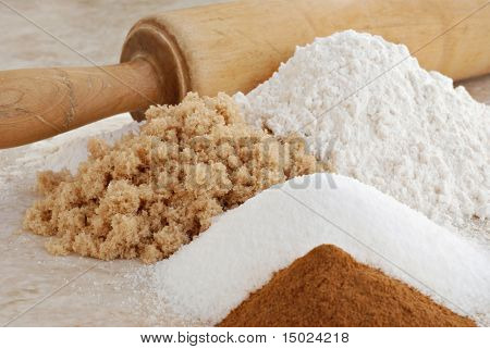 Baking ingredients with vintage rolling pin.  Close-up with shallow dof.  Focus on brown sugar.