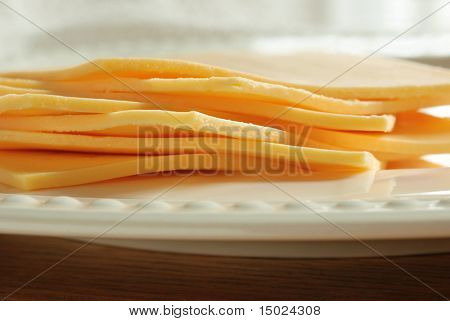 Stack of sliced deli cheese on a porcelain plate.  Macro with extremely shallow dof.