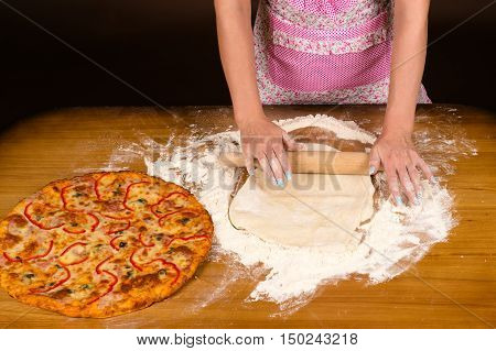 woman in apron preparing pizza on table