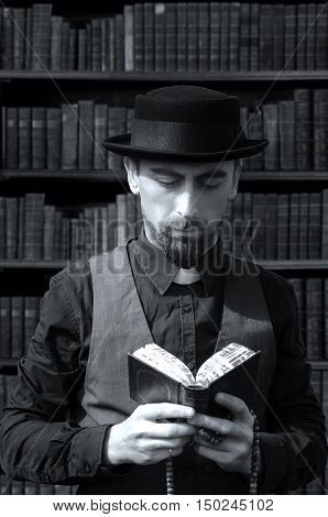 Young bearded priest reads bible on book background. Black and white photography