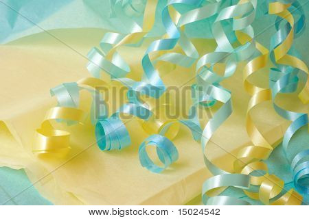 Pastel colored curly ribbons on matching tissue paper.  Macro with shallow dof.  Ideal as background