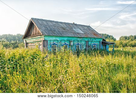old bright green abandoned wooden house on sunny summer day