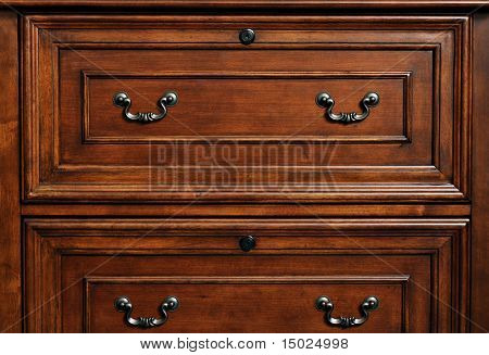 Beautifully crafted wood furniture. Detail of closed drawers with ornate pewter handles.