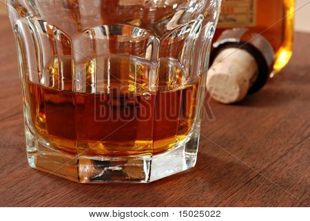 Backlit glass of whiskey with bottle and cork stopper in the background.  Macro with shallow dof.