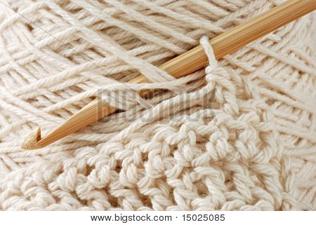 Extreme macro of bamboo crochet hook, spool of natural cotton thread and detail of stitches.