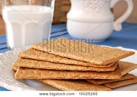 Graham crackers on vintage plate with pitcher and glass of milk in background.  Close-up with shallow dof.