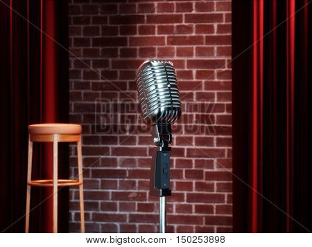 Vintage metal microphone against red curtain on empty theatre stage. 3D illustration