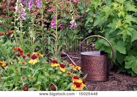 Bronze metal watering can in flower garden.  Shallow dof with focus on the can.