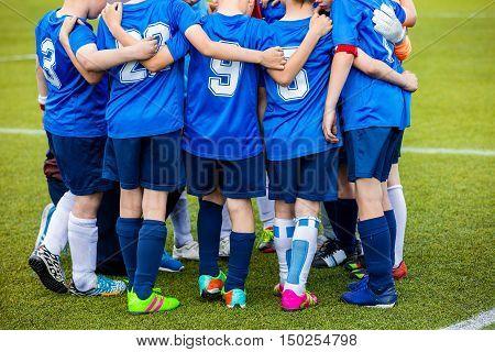 Hapy young football soccer team with coach standing together before match on sports field