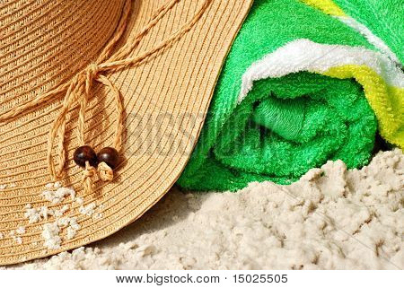 Summer straw hat with colorful beach towel on sandy beach.  Macro with shallow dof.