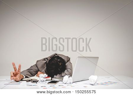 Tried overworked businessman sleeping while showing victory gesture on the office table. Keep fighting in business concept.