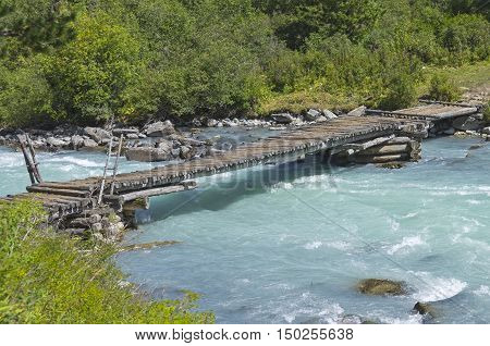 Old wooden bridge at the end of the Kucherla lake whence the river Kucherla follows. Altai Mountains Russia. Sunny summer day.