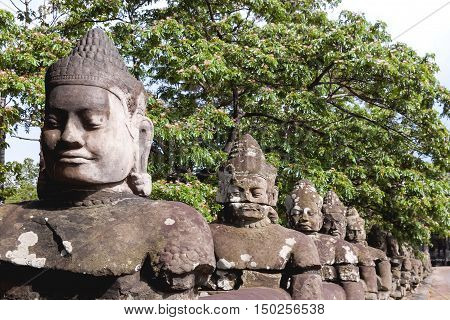 Stone sculptures near South Gate of Angkor Thom from outside the city. Angkor Wat. Siem Reap Cambodia. UNESCO World Heritage Site.
