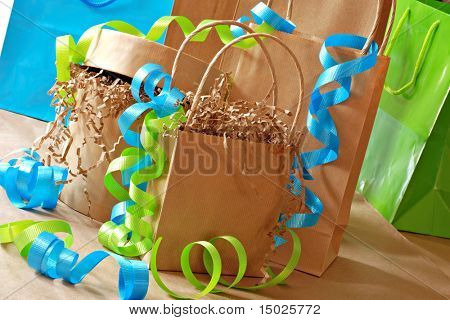Simple brown paper gift bags and boxes decorated with colorful curling ribbon.  Close-up with shallow dof.