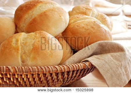 Basket of freshly baked dinner rolls with tableware in background. Macro with shallow dof.