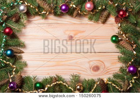 frame of fir branches decorated with toys and serpentine on a light wooden background.