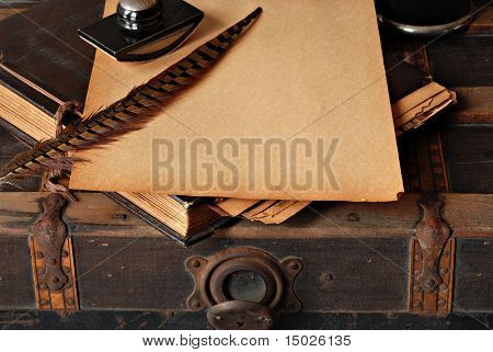 Vintage background with old scrapbook and writing supplies on rustic steamer trunk.   Copy space on yellowed pages of scrapbook.