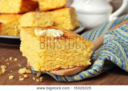 Still life of freshly baked homemade cornbread with butter melting on top.  Close-up with shallow dof.