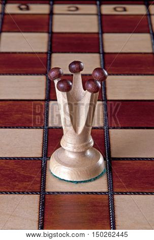 White Queen chess piece isolated on a chessboard