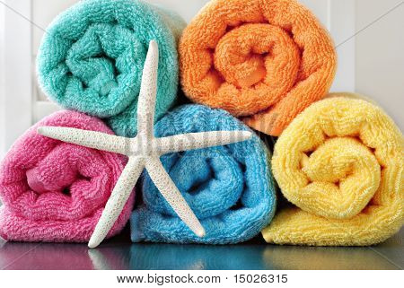 Colorful still life of towel rolls with white finger starfish on reflective surface.
