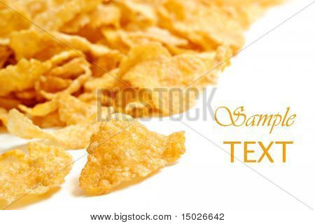 Golden crispy corn flakes on white background with copy space.  Macro with extremely shallow dof.