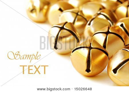 Shiny gold jingle bells on white background with copy space.  Macro with shallow dof.