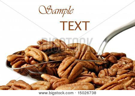 Pecan halves spilling from stainless steel scoop on white background with copy space.  Macro with shallow dof.