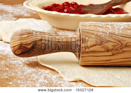 Beautiful olive wood rolling pin with homemade pie crust and cherry filling.  Macro with shallow dof.