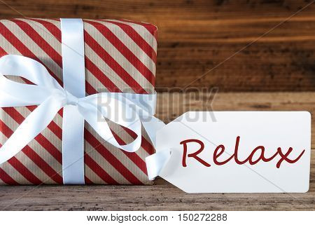 Macro Of Christmas Gift Or Present On Wooden Background. Card For Seasons Greetings, Best Wishes Or Congratulations. White Ribbon With Bow. English Text Relax