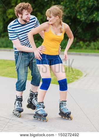 Holidays active people and friendship concept. Young fit couple on roller skates riding outdoors woman and man rollerblading together on city street