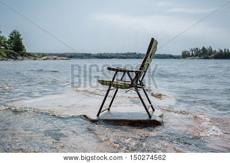patio chair standing on rock surface stone beach against lake and sky background