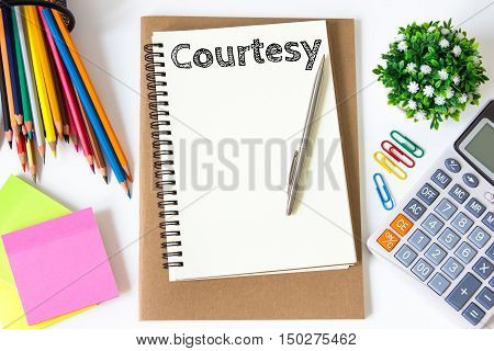 courtesy text message on white paper and office supplies, pen, paper note, on white desk , copy space / business concept / view from above, top view