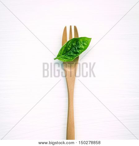Closeup  Fresh Sweet Basil Leaves With Fork  On White Wooden Background. Sweet Basil Leaves With Fla