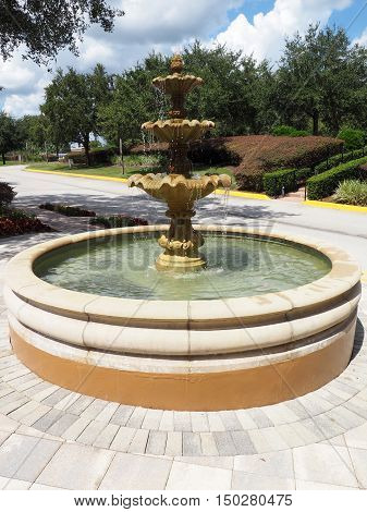 an ornate round water fountain on a beautiful sunny day