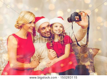 family, christmas, x-mas, winter, happiness and people concept - smiling family in santa helper hats taking picture with photo camera