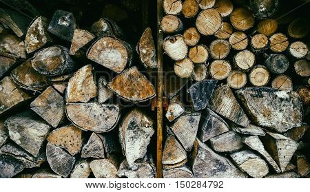 Dramatic horrifying wall of decaying vintage firewood logs stacked in an old haunted wood shed.