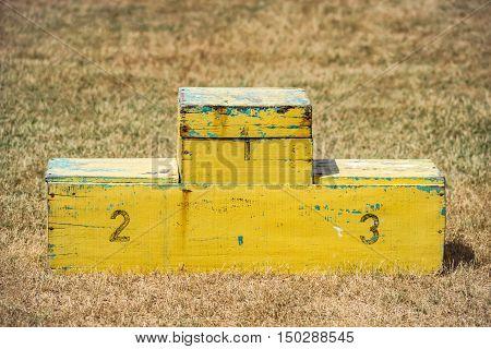 Handmade podium yellow outdoors wooden pedestal contest ceremony sports position empty
