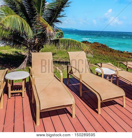 Loungers on the deck by the seafront Tobago Caribbean square composition