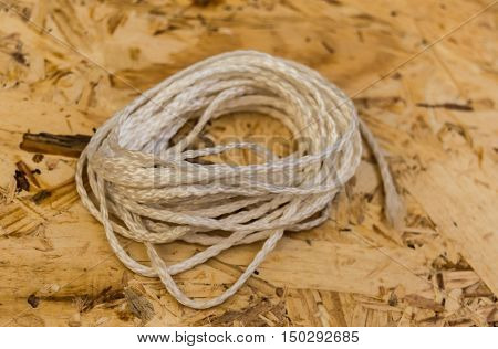 White clothesline on chipboard background. Close-up. Horizontal.