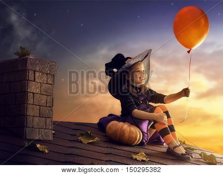 Happy Halloween! Cute little witch with a air ball. Beautiful young child girl in witch costume outdoors.