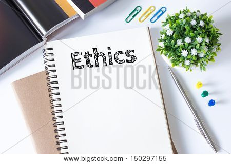 ethics word message on white paper book and copy space on white desk / business concept / top view
