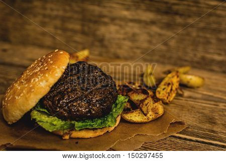 Grilled beef hamburger with potato on wood table
