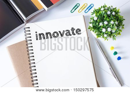 innovate word message on white paper book and copy space on white desk / business concept / top view