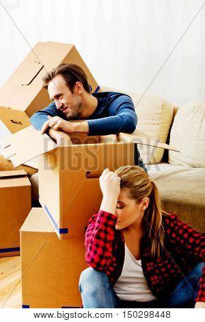 Tired couple sitting among carton boxes