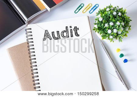 Text Audit on white paper book and office supplies on white desk / business concept