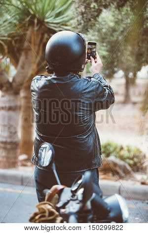 Back view of man in leather jacket and bike helmet taking self-portrait via phone