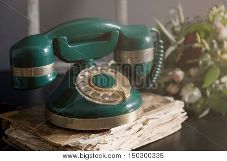 Old telephone and directory on table, closeup