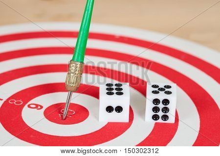Dice on dart board with green dart arrow